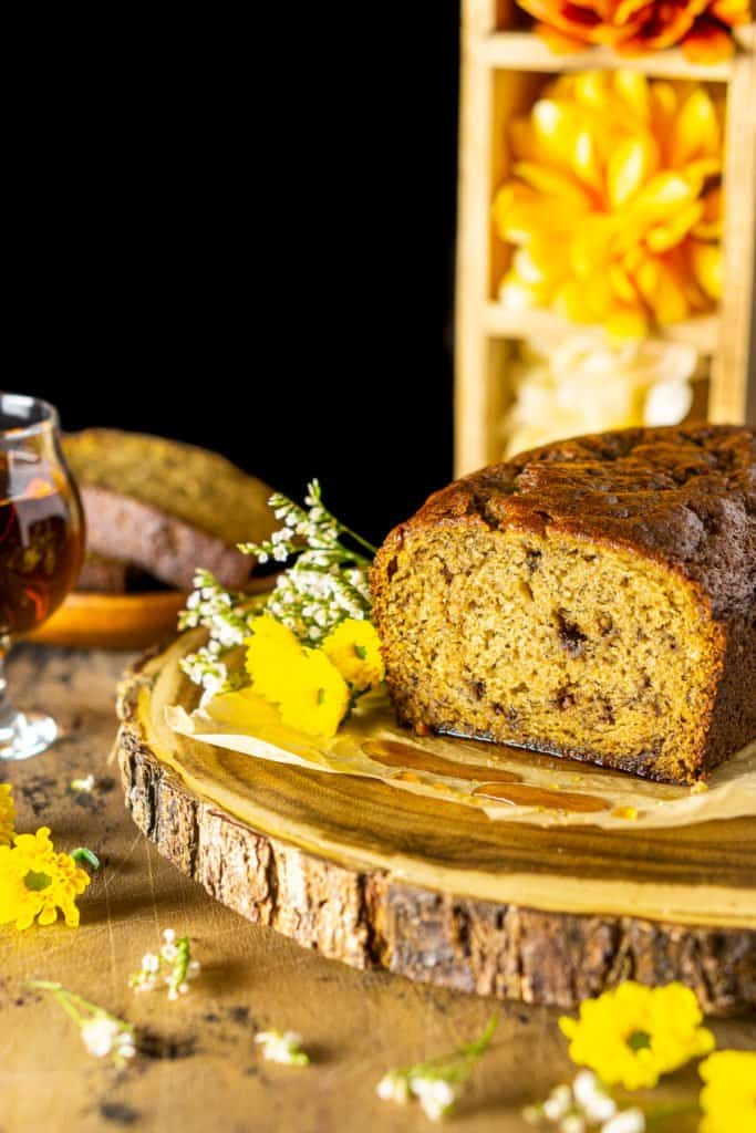 The maple-bourbon banana bread with a stack of flowers in the background.