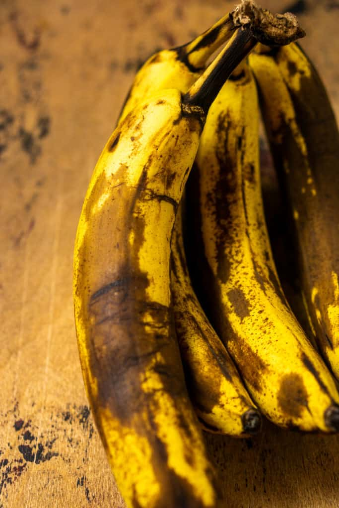 Bananas that have been ripened and show off large brown spots all over the fruit.