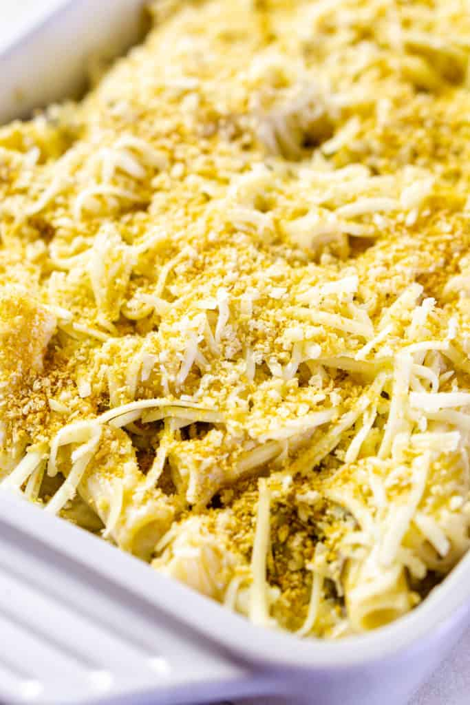 The pasta layered with the cheese sauce and ricotta mixture and topped with panko and more cheese in a baking dish.