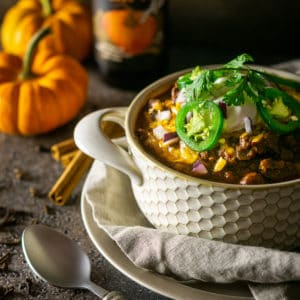 A bowl of pumpkin and chorizo chili with two small pumpkins and a pumpkin beer in the background with a spoon to the side.