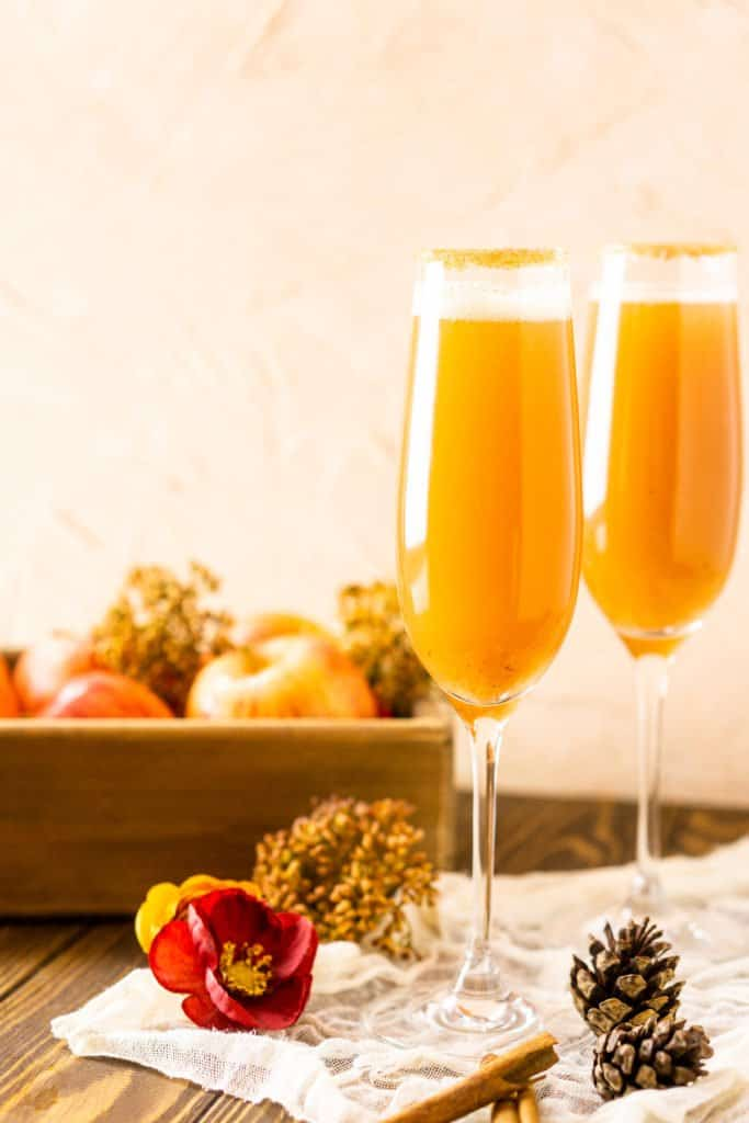Two apple Bellinis from the side with a box of apples behind them.