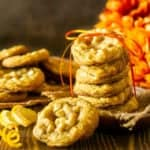 A stack of ginger-maple cookies with orange zest tied with a ribbon and orange flowers in the background.