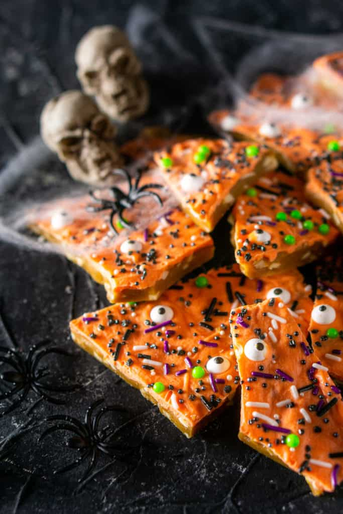 The Halloween toffee piled on top of each other with decorations on the side.