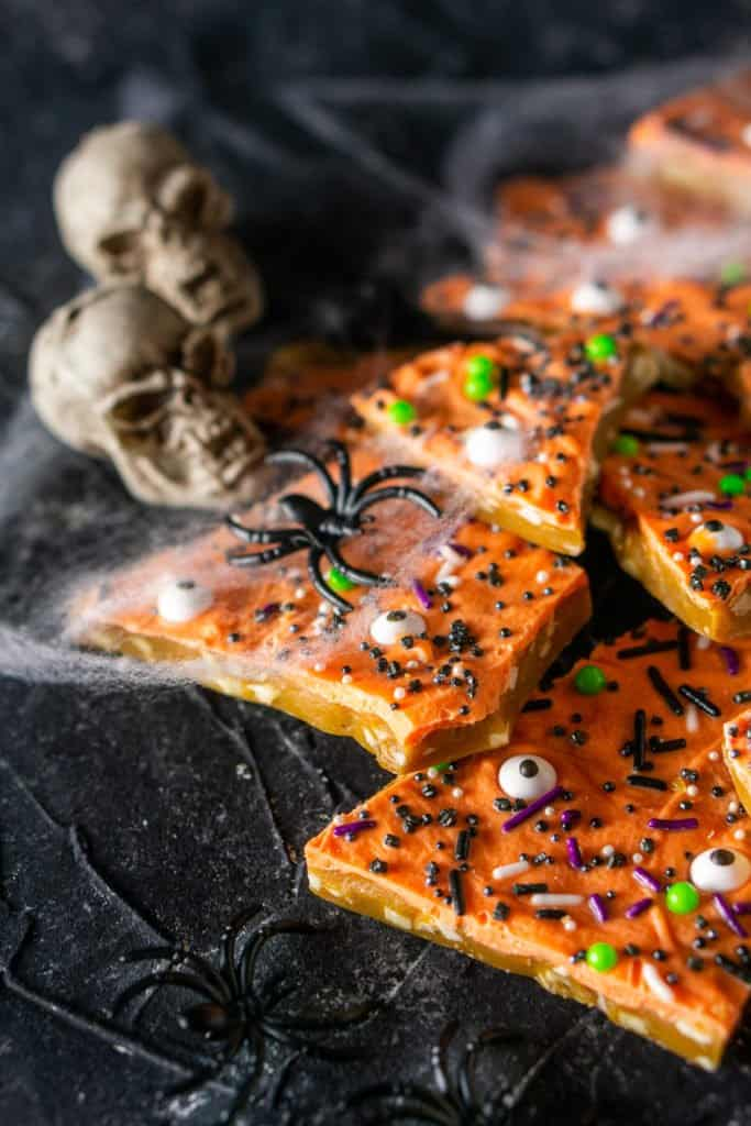 A pile of Halloween toffee with plastic spiders on the side.