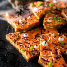 A pile of Halloween toffee with spider webs, plastic spiders and skulls in the background.