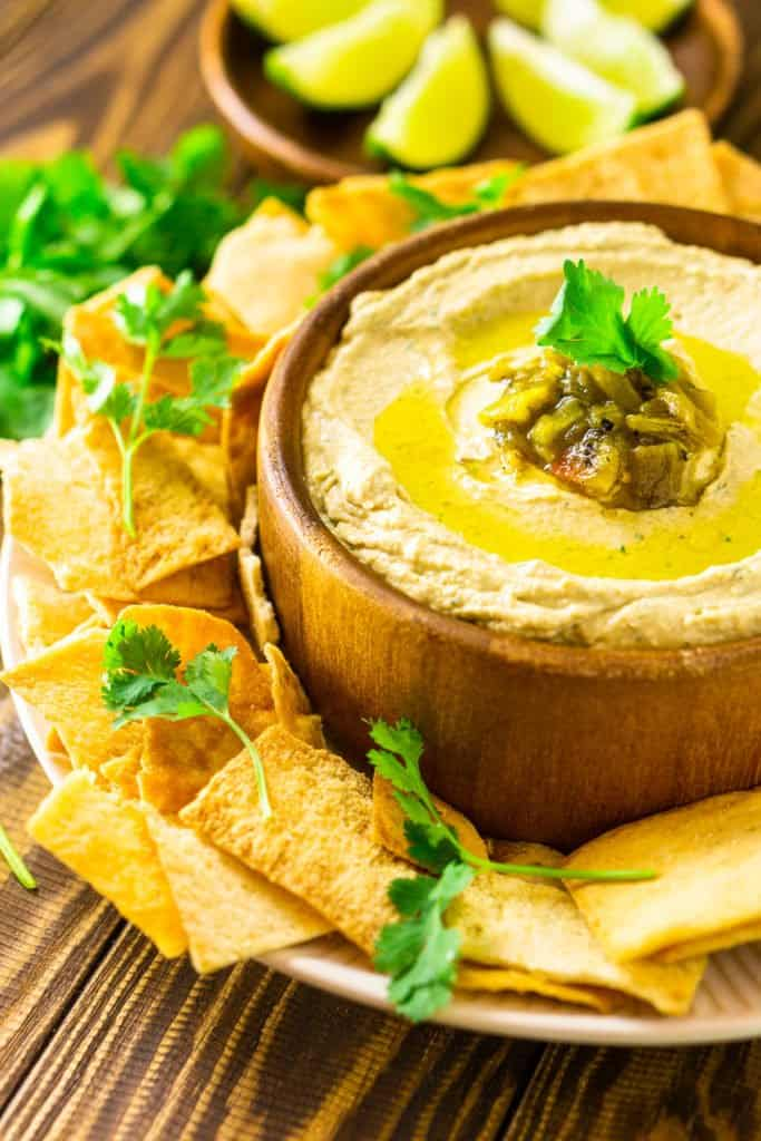 A side view of a bowl of Hatch green chile hummus with a plate of lime slices in the background.