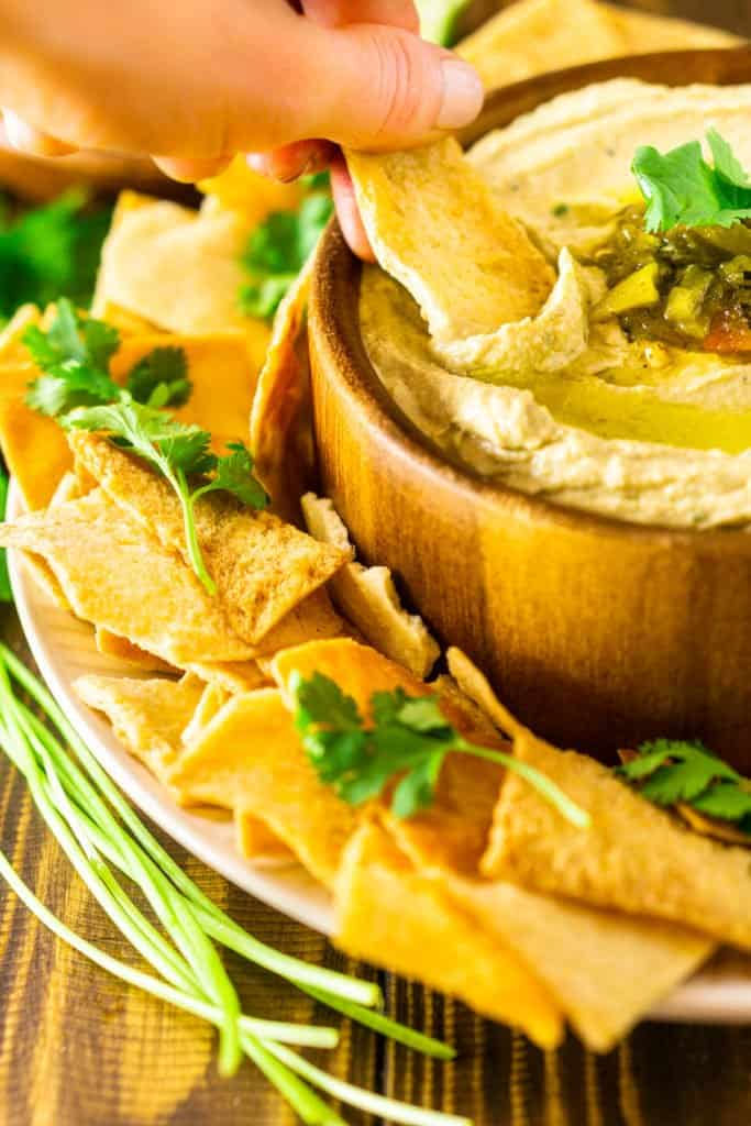 A person dipping a pita chip into the bowl of Hatch green chile hummus.