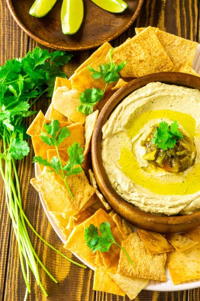 An aerial view of the Hatch green chile hummus in a wooden bowl with cilantro on the side.