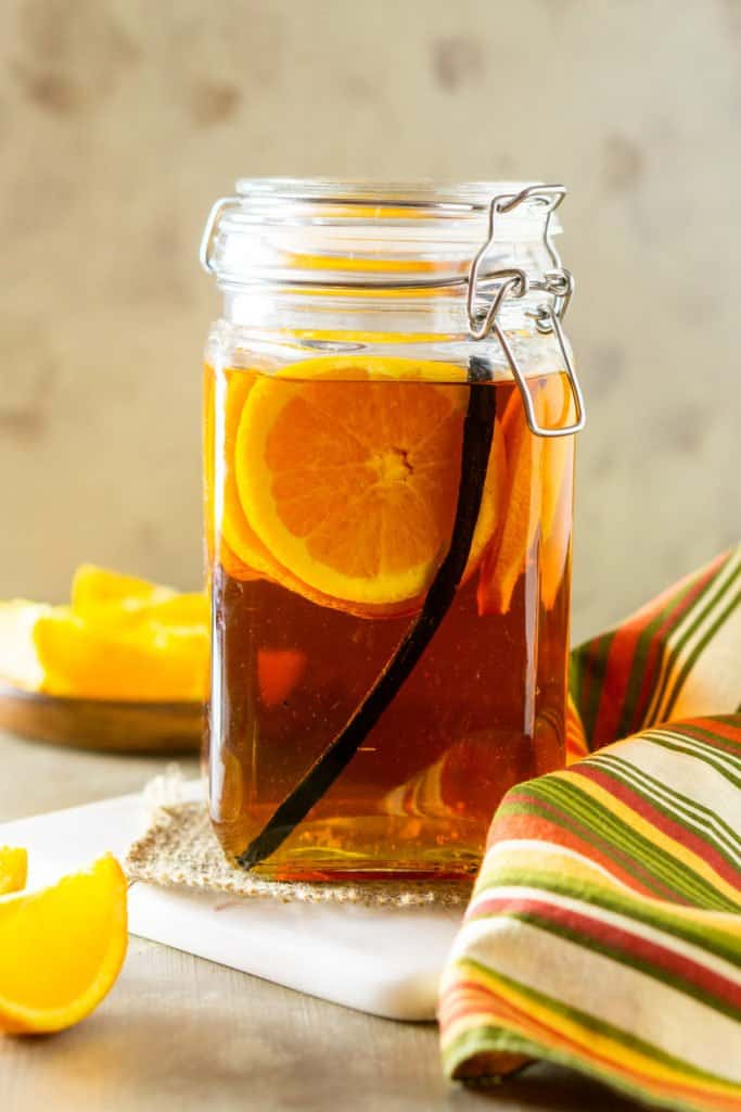 A jar of vanilla bean and orange infused bourbon with orange slices and a cloth napkin to the side.
