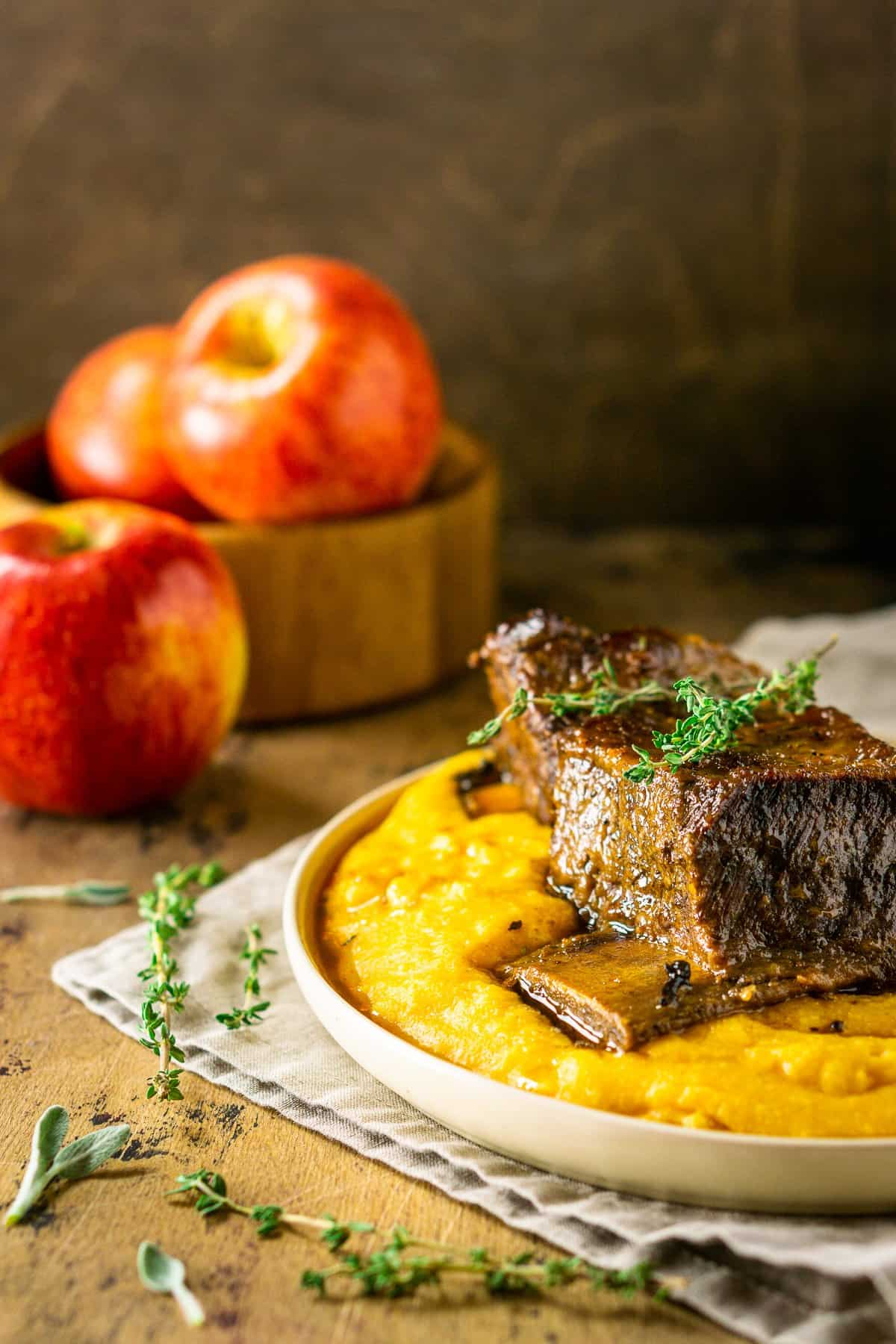 A plate of polenta with a braised apple cider short rib with fresh herbs around it.