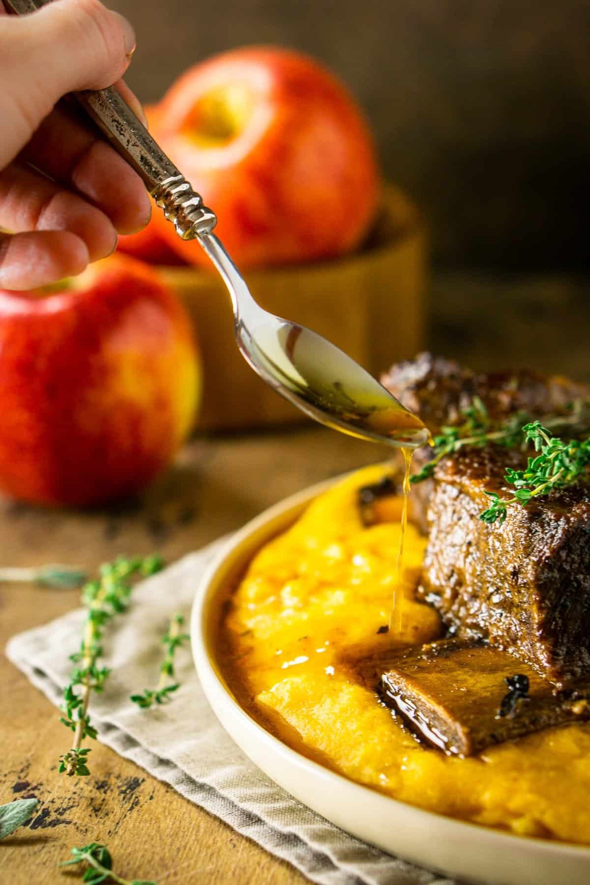 Pouring a spoonful of the sauce onto the polenta and apple cider short ribs.