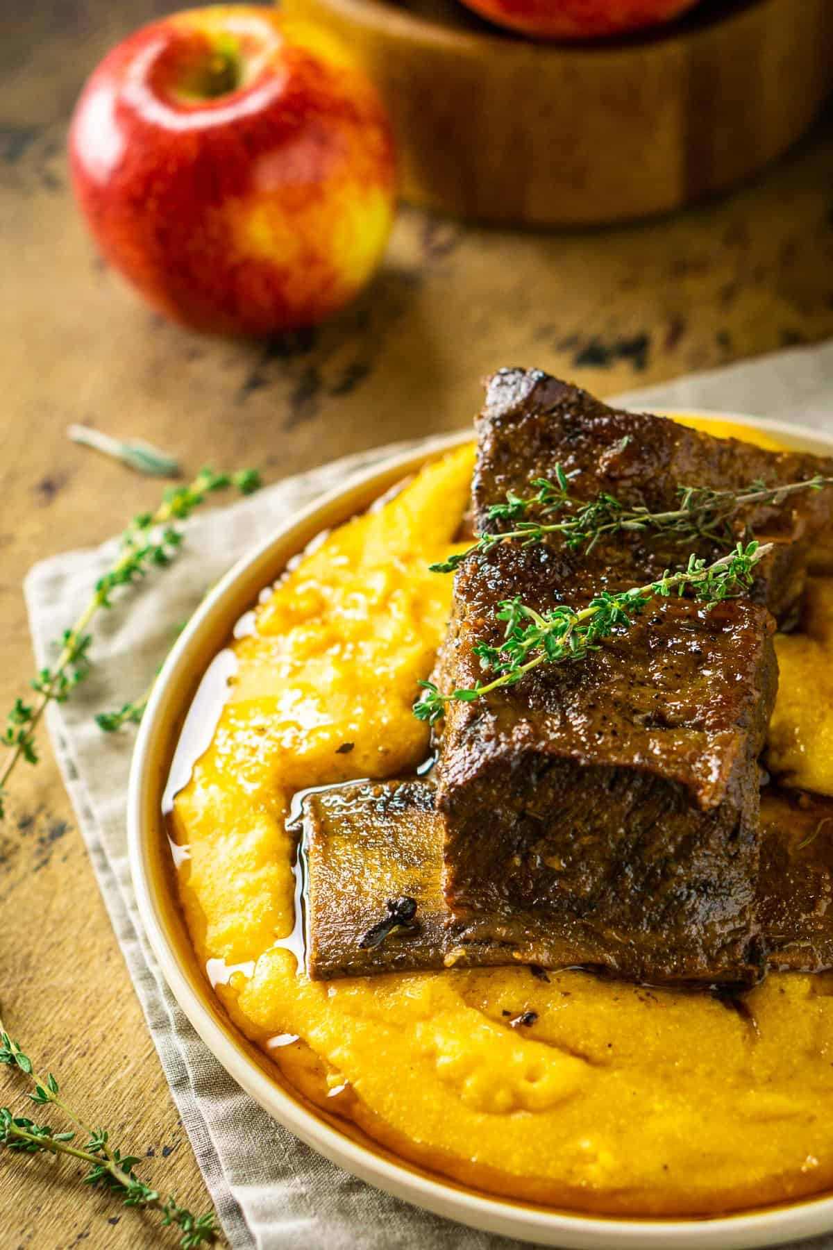 Looking down on two braised apple cider short ribs with an apple to the side.