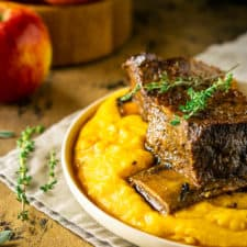 Two braised apple cider short ribs on polenta with fresh herbs to the side and apples in the background.