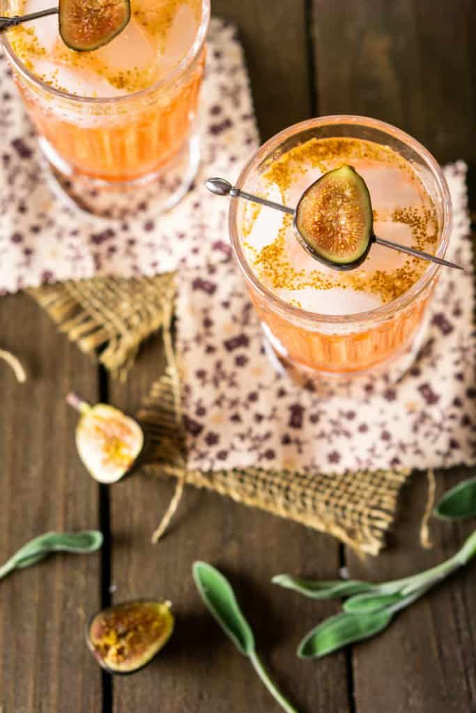Two sage and fig cocktails from an aerial view on burlap with sliced figs on the side.