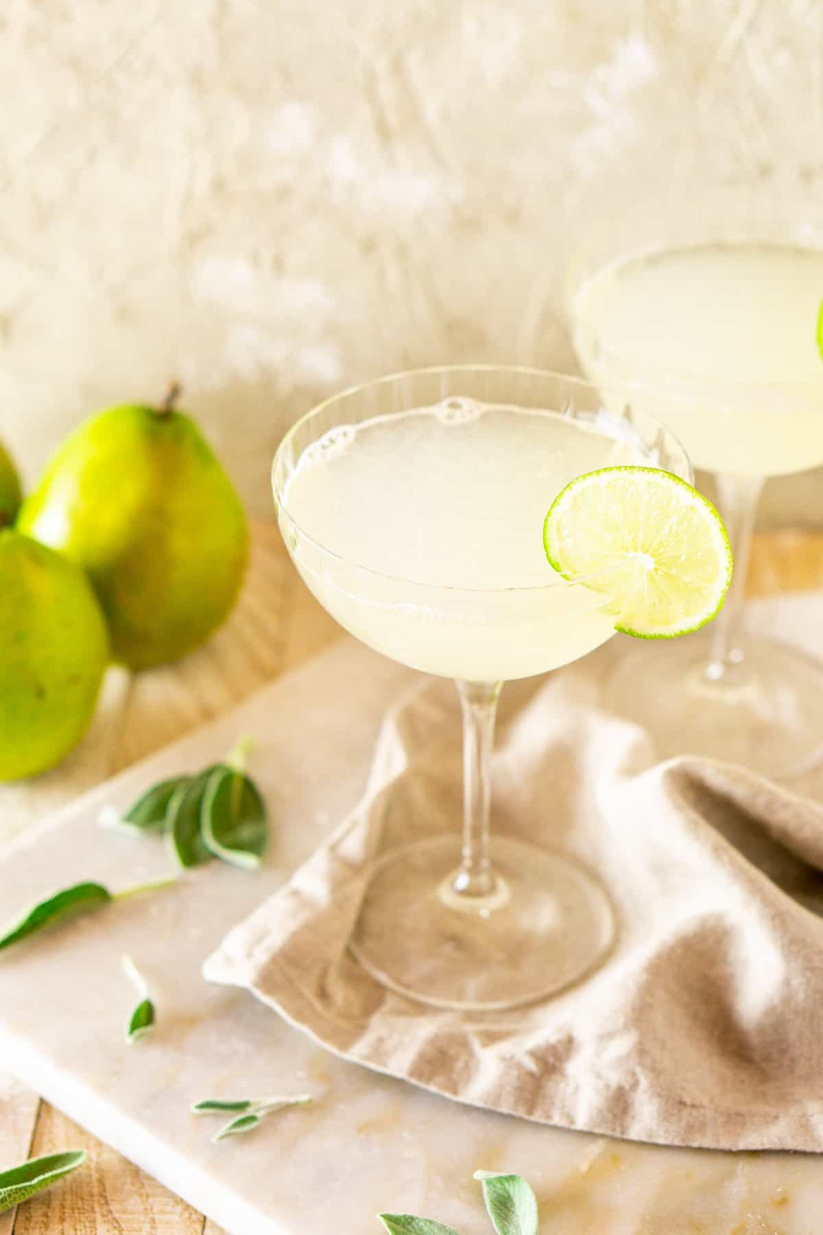 A close-up shot of the gimlet with pears to the side on a white marble board.
