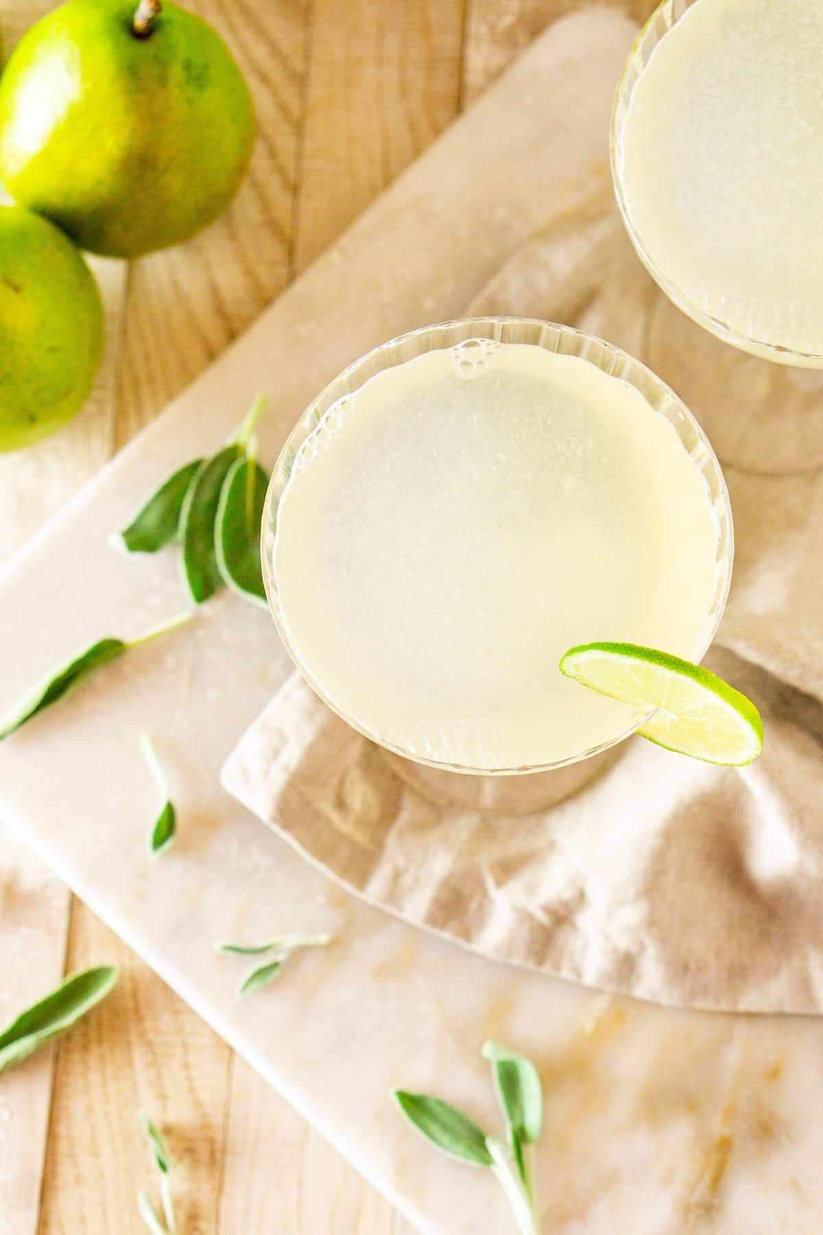 An aerial view of a pear-sage gimlet with fresh sage leaves surrounding it.