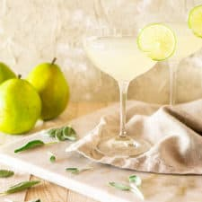 Two pear-sage gimlet cocktails on a marble board with fresh sage around it and pears in the background.