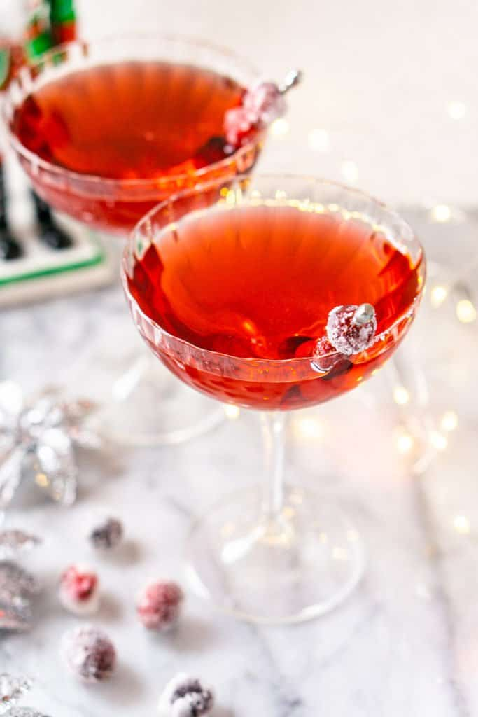 Looking into two Sugar Plum Fairy Martini with a nutcracker and sugared cranberries.