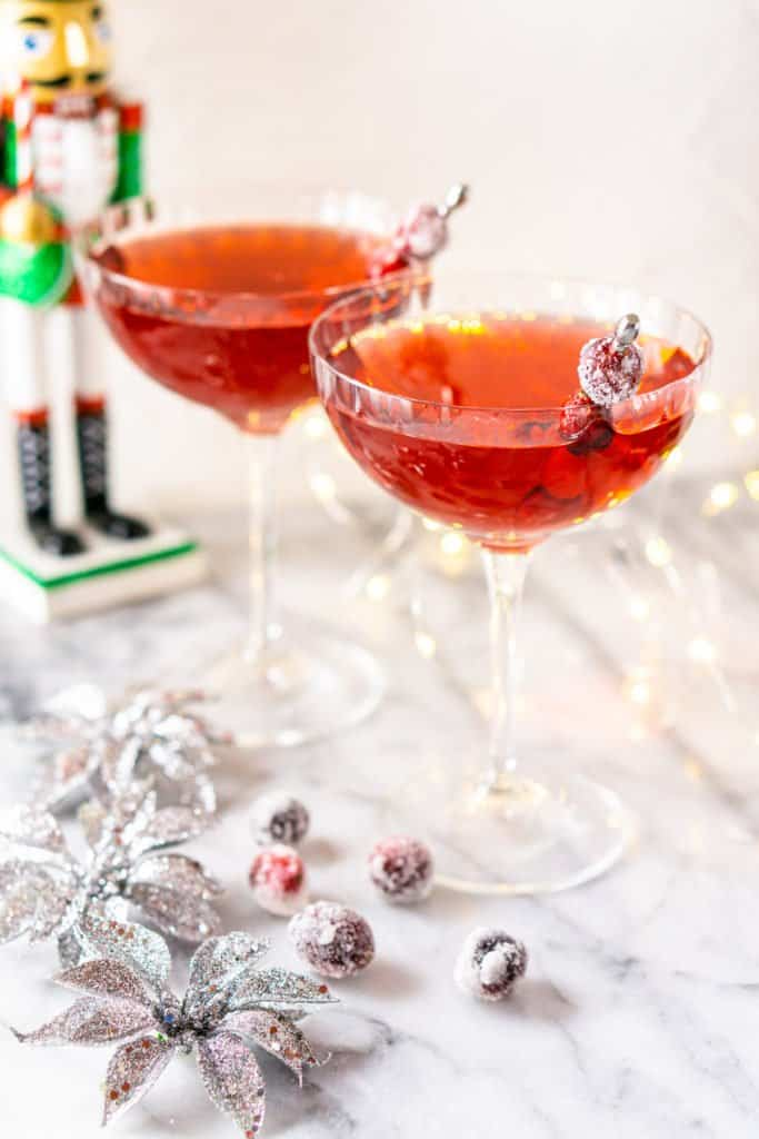 Looking down at two Sugar Plum Fairy Martinis with silver ornaments and sugared cranberries on a marble board.