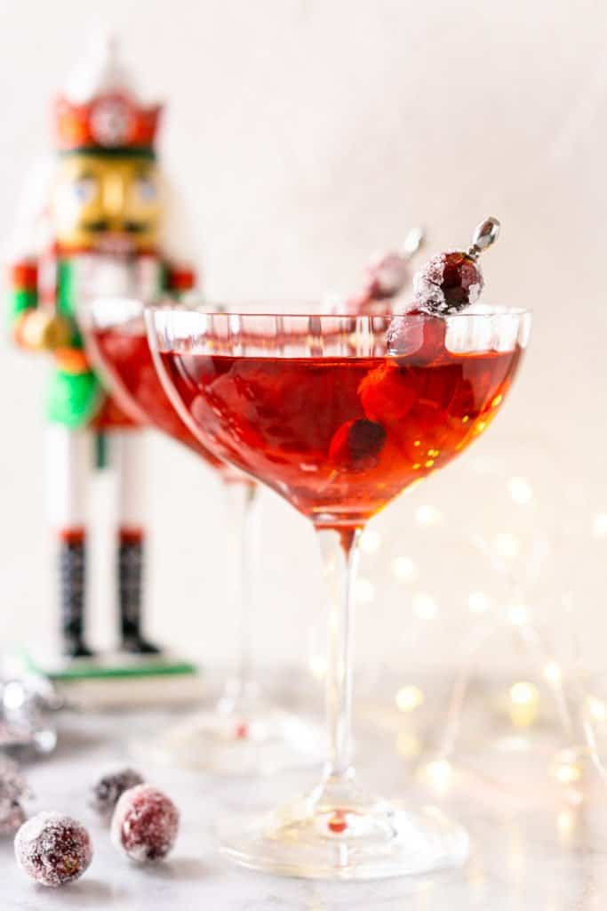 A close-up of a Sugar Plum Fairy Martini with sugared cranberries and lights.