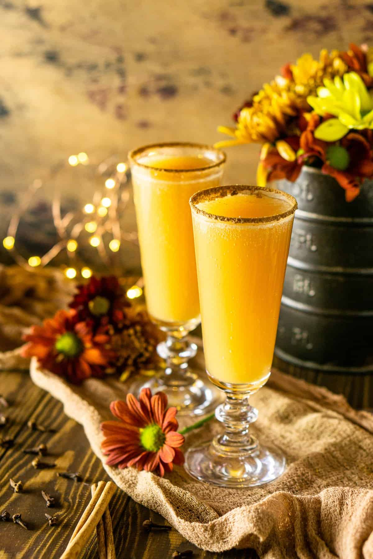 A side shot of two Thanksgiving mimosas on cheesecloth with cinnamon sticks and lights next to it.