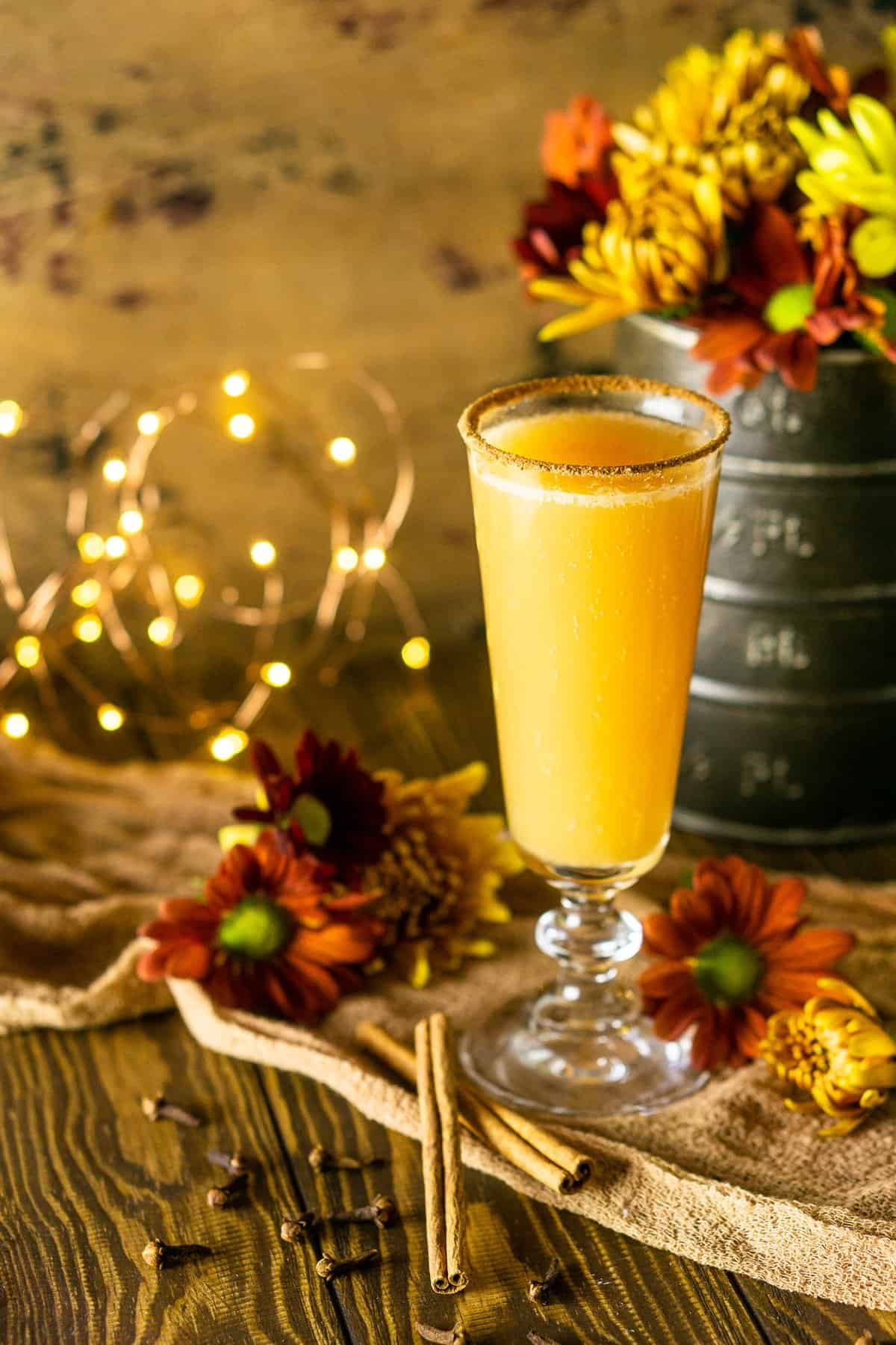 A single Thanksgiving mimosa in front of fall flowers with lights to the side.