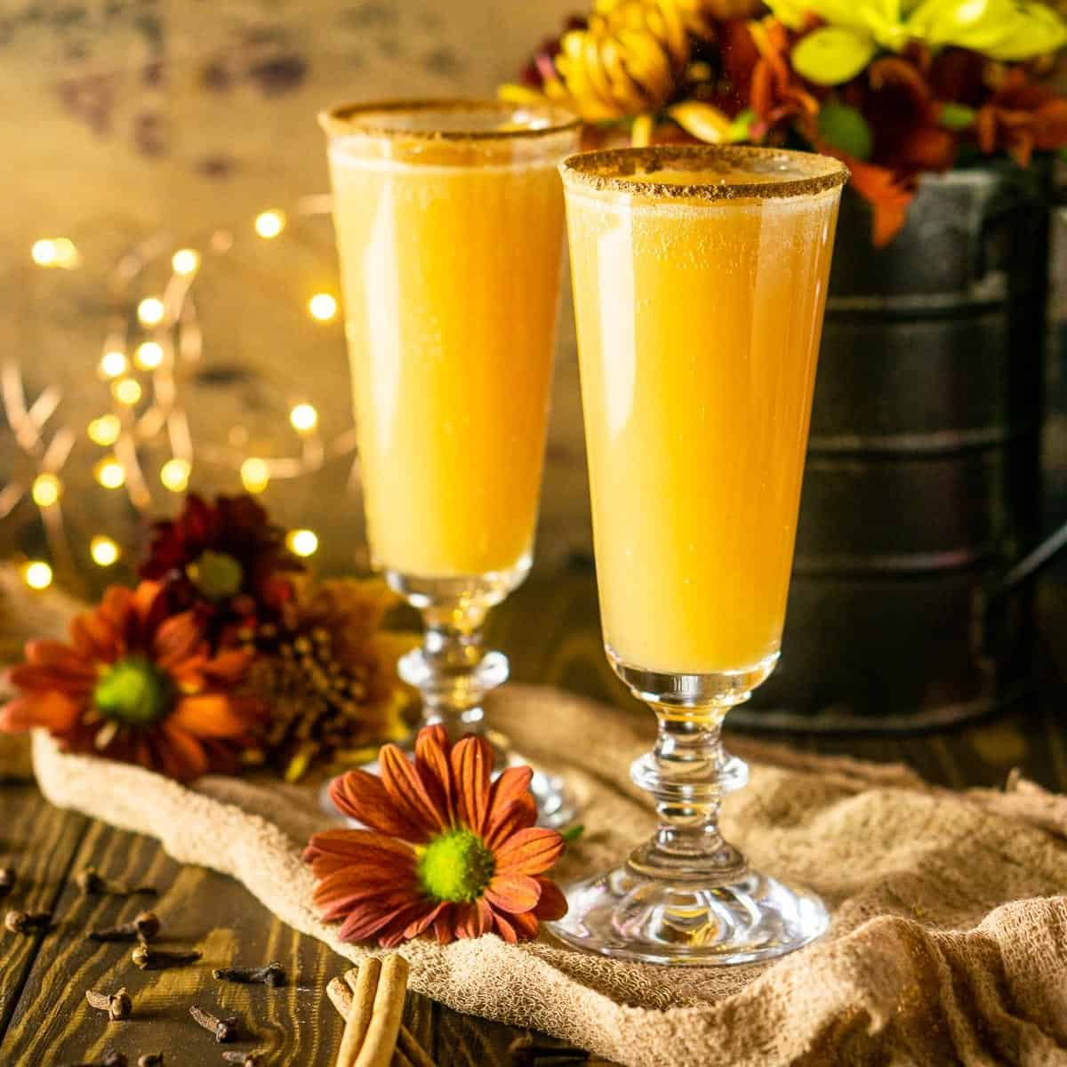 Two Thanksgiving mimosas with fall flowers and lights behind it with cinnamon sticks and cloves to the side.