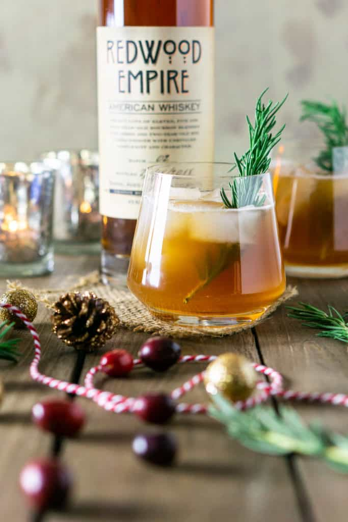 A chai-cranberry bourbon smash in front of a bottle of bourbon with Christmas string, cranberries and rosemary around it.