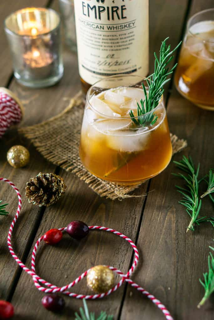 Two holiday bourbon smashes on burlap with festive decor around it.