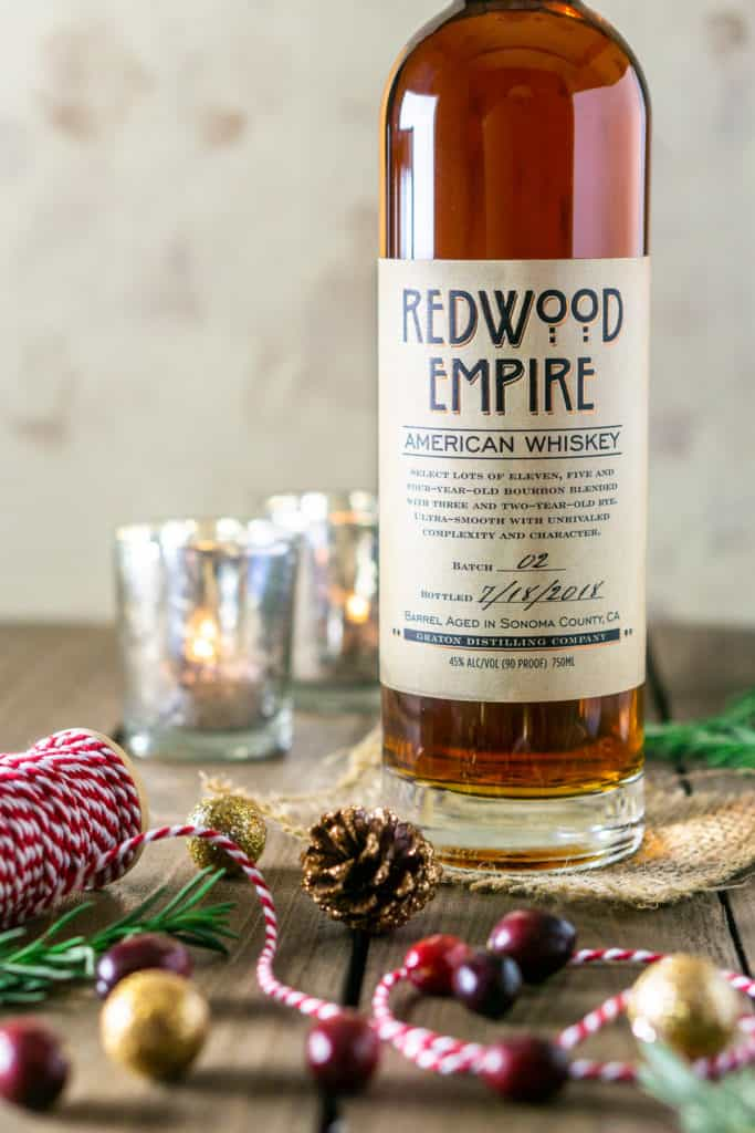 A bottle of Redwood Empire bourbon with Christmas decor around it.