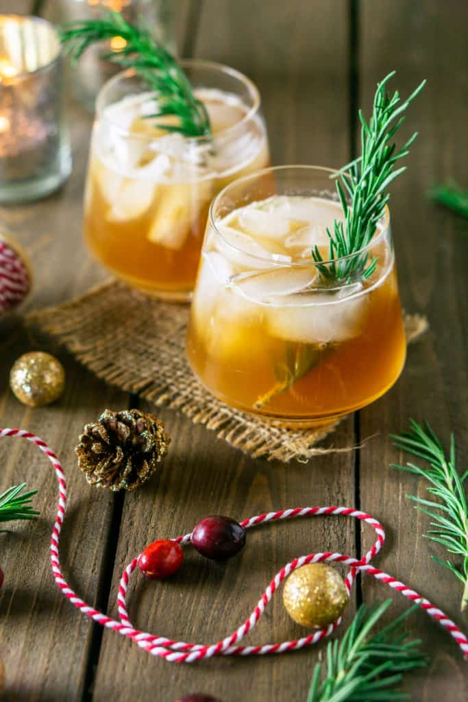 Two chai-cranberry bourbon smashes on burlap with a candle to the side.