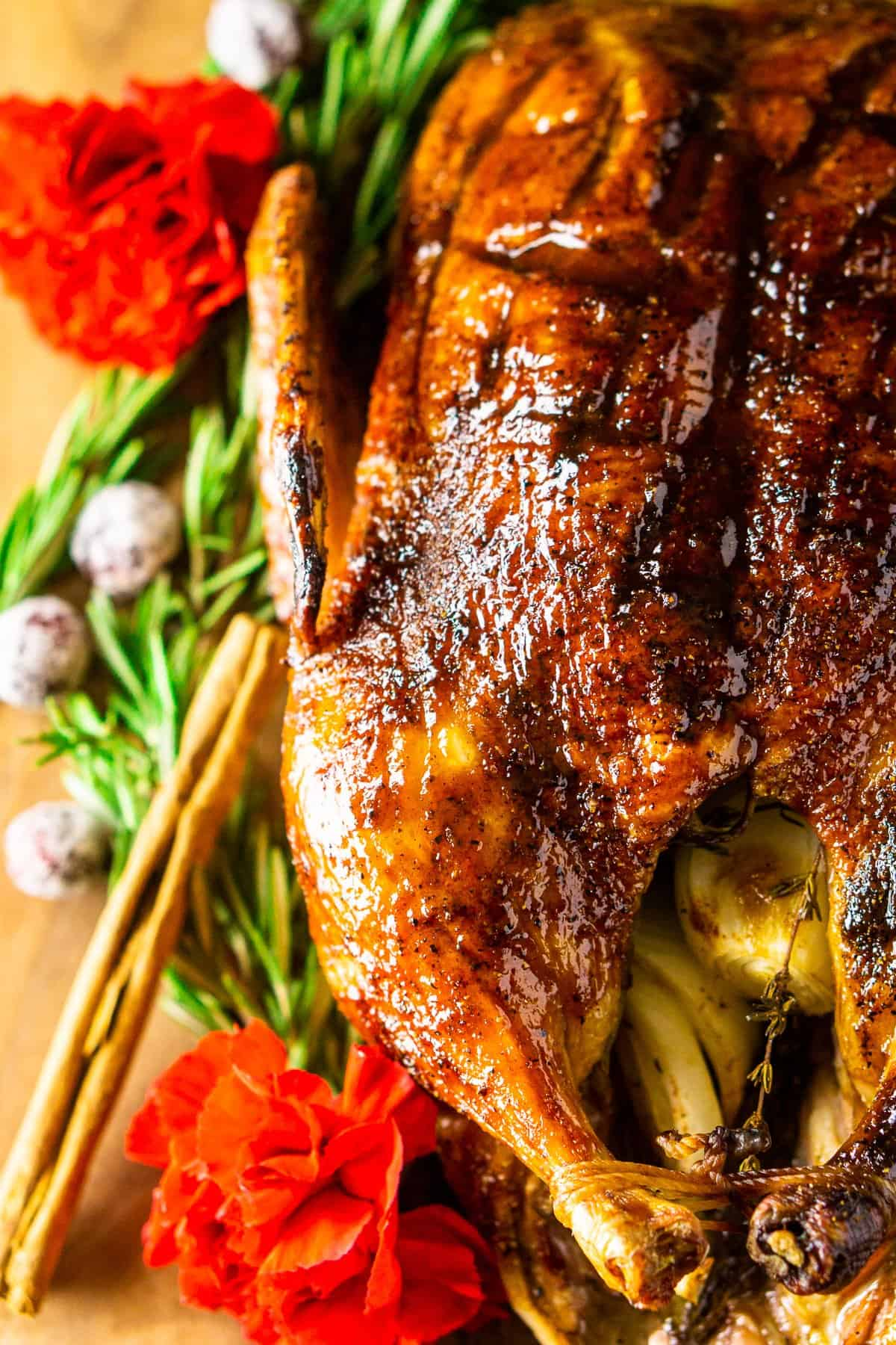 The roasted holiday duck on a bed of rosemary with cinnamon sticks and flowers to the side.