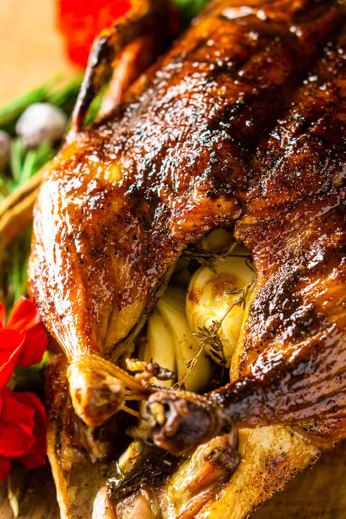 Looking down on the roasted duck from the side with rosemary sprigs in the background.