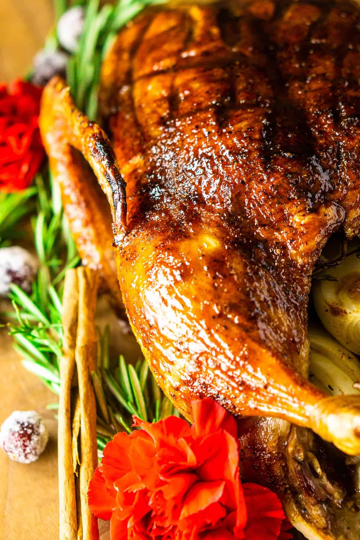 The Christmas roast duck with holiday decor around it on a cutting board.
