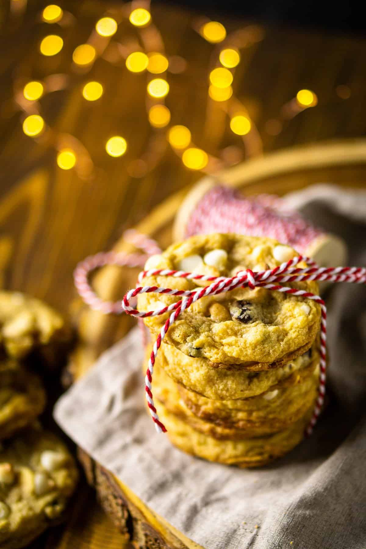 A stack of cranberry-orange cookies tied with a red and white string and lights in the background.