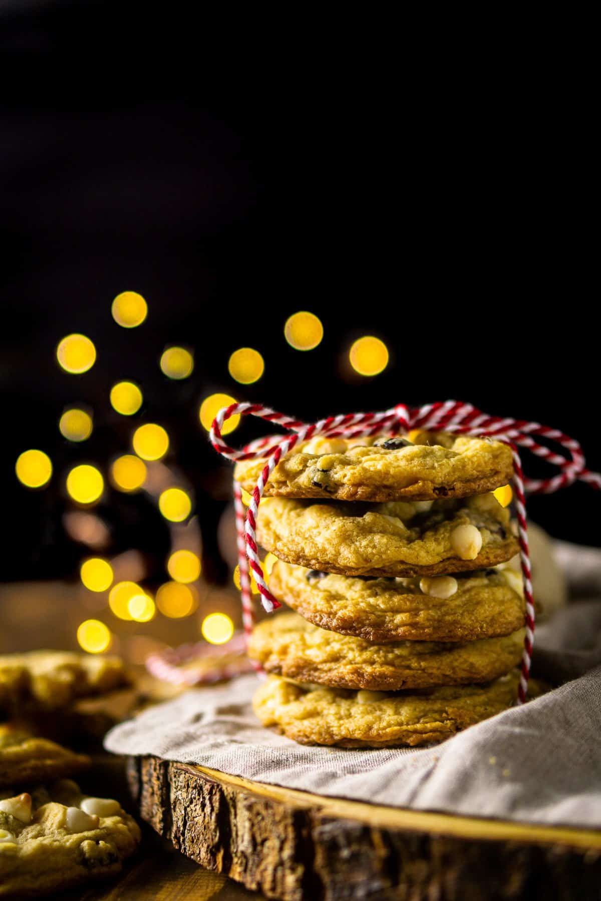 Looking straight on to a stack of cranberry-orange cookies with a black background and lights behind it.
