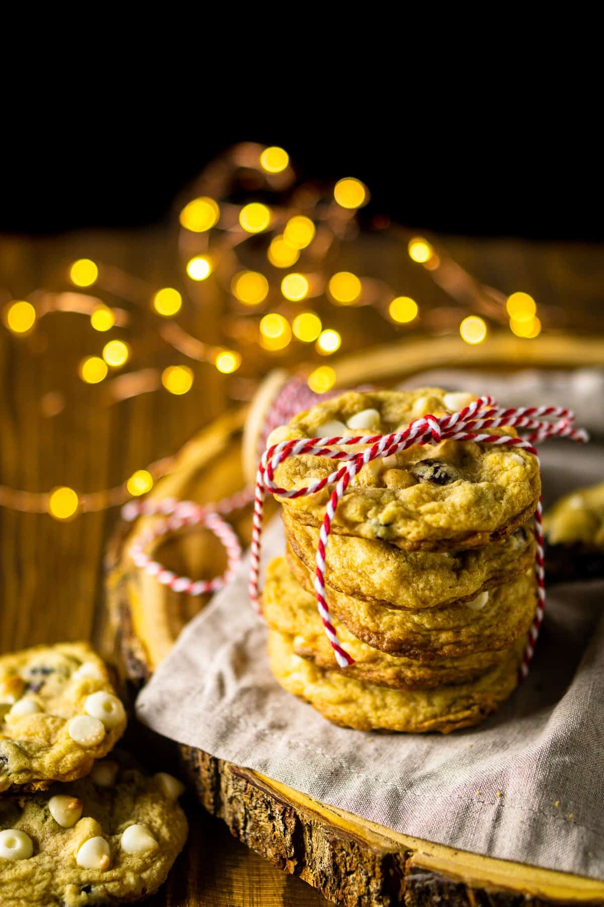 Looking down on a stack of cranberry-orange cookies with white chocolate chips on a wooden serving board with lights behind it.