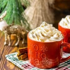 Two mugs of this homemade gingerbread latte with cinnamon sticks to the side and Christmas decor in the background.