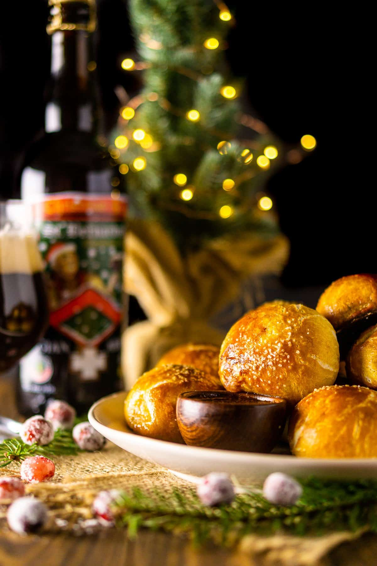 Looking straight on to a plate of holiday pretzel bites with a small Christmas tree and beer in the background.