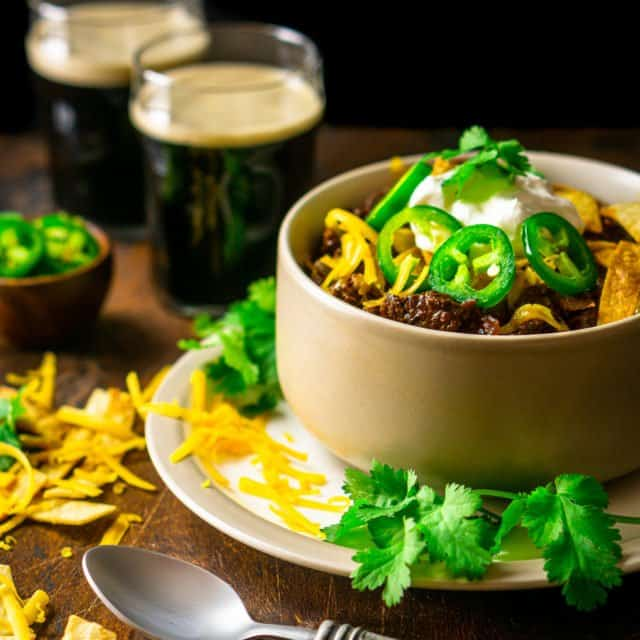 A bowl of authentic Texas chili with cilantro, cheese and two stouts in the background.