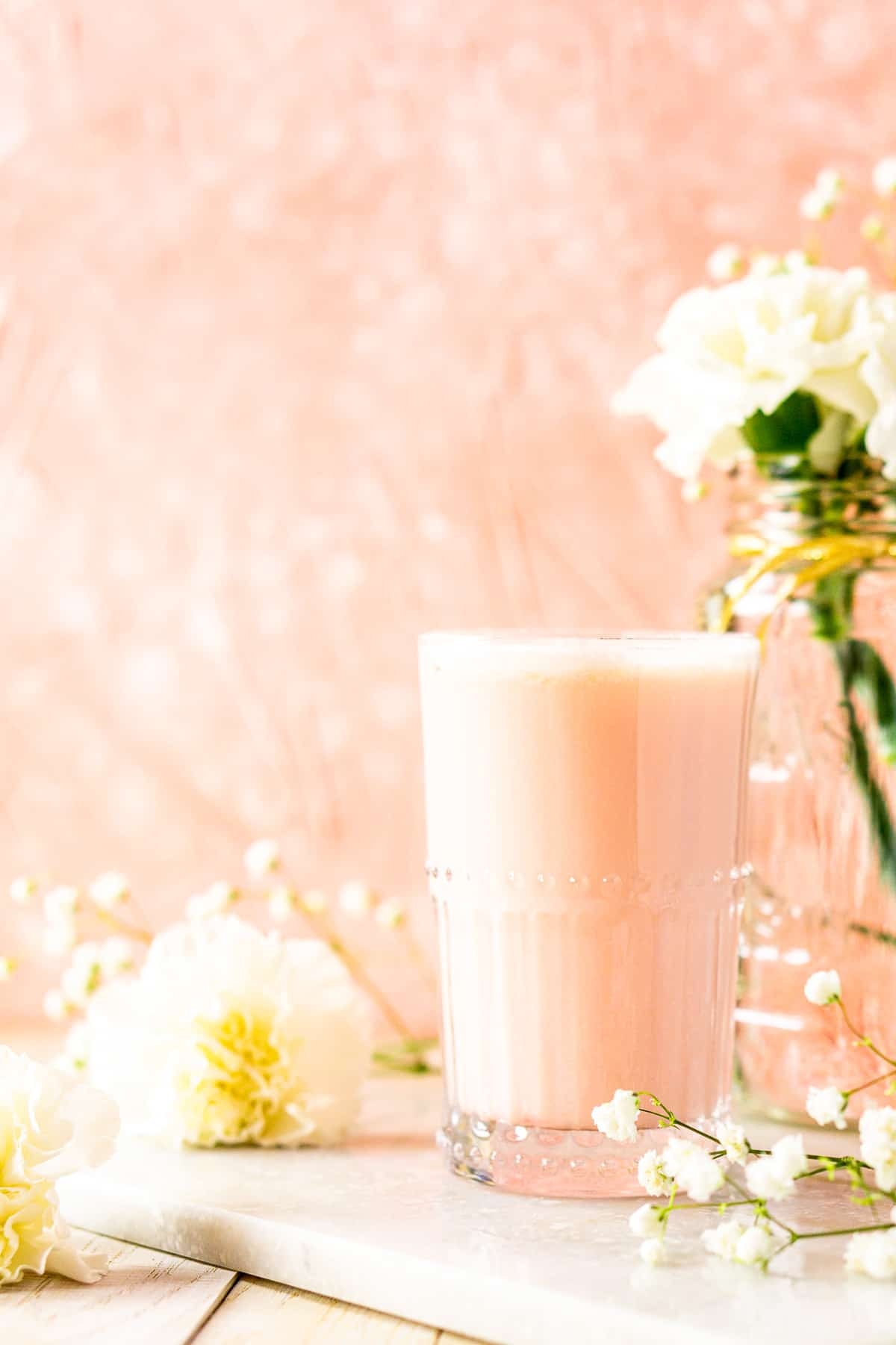 Looking straight on to the blood orange gin fizz with white flowers and a pink background.