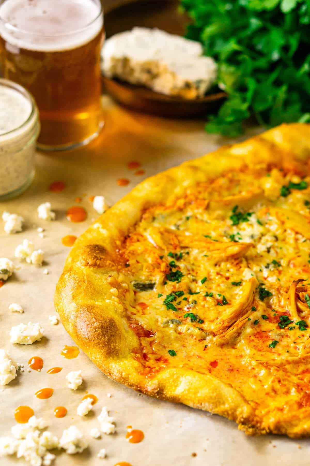 The Buffalo chicken pizza on parchment paper with ranch and a beer to the side with a slab of blue cheese and fresh parsley.