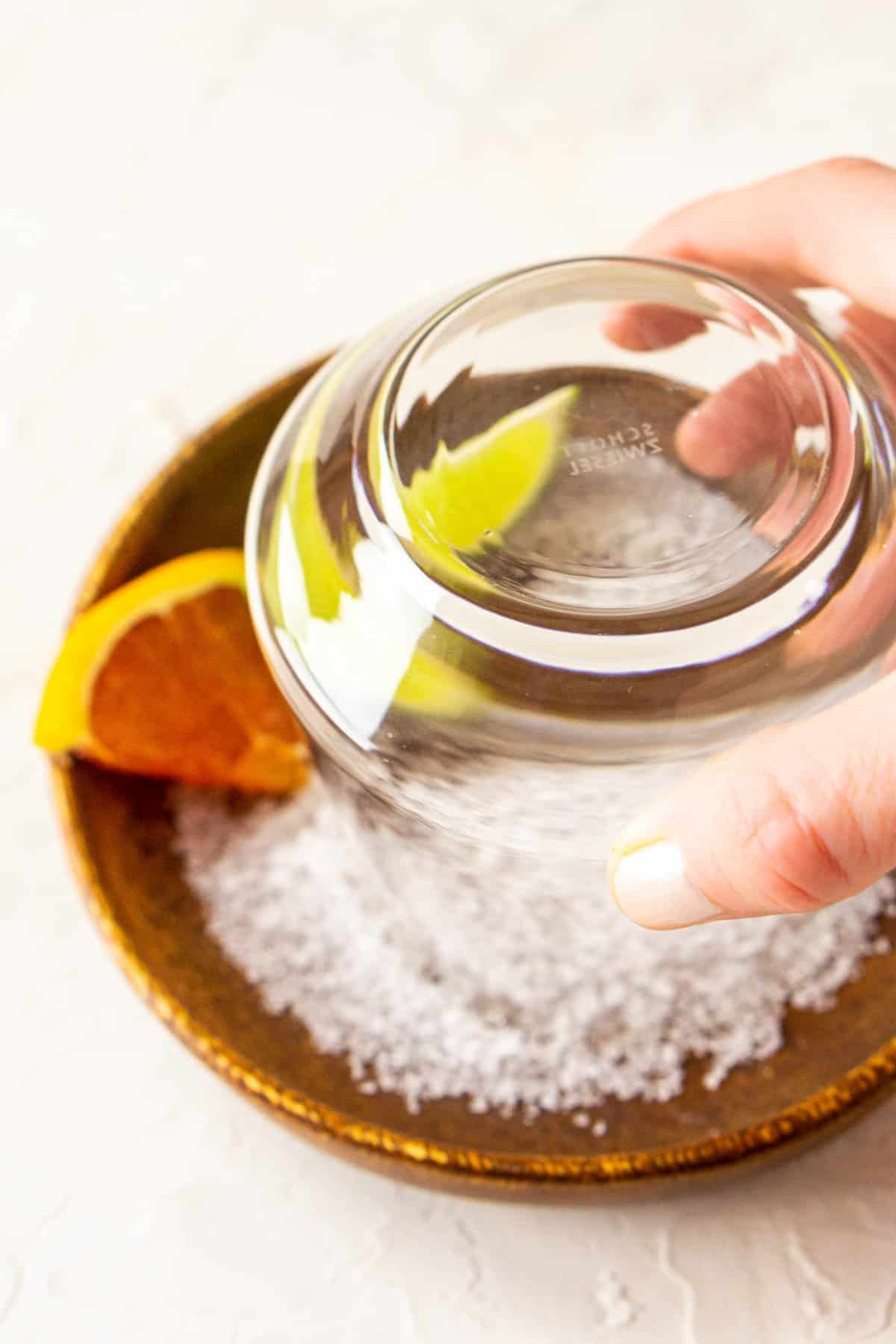 A glass in a plate of salt to show the process of how to rim a margarita glass with salt.