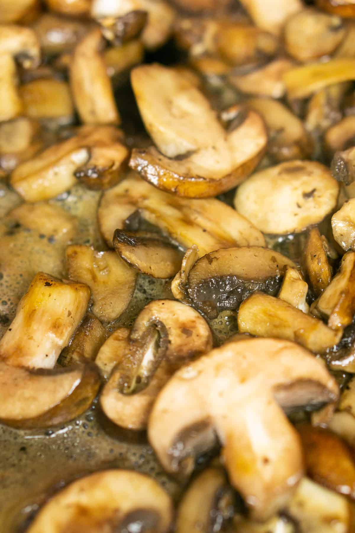 Cooking the mushrooms in a large skillet until they brown.