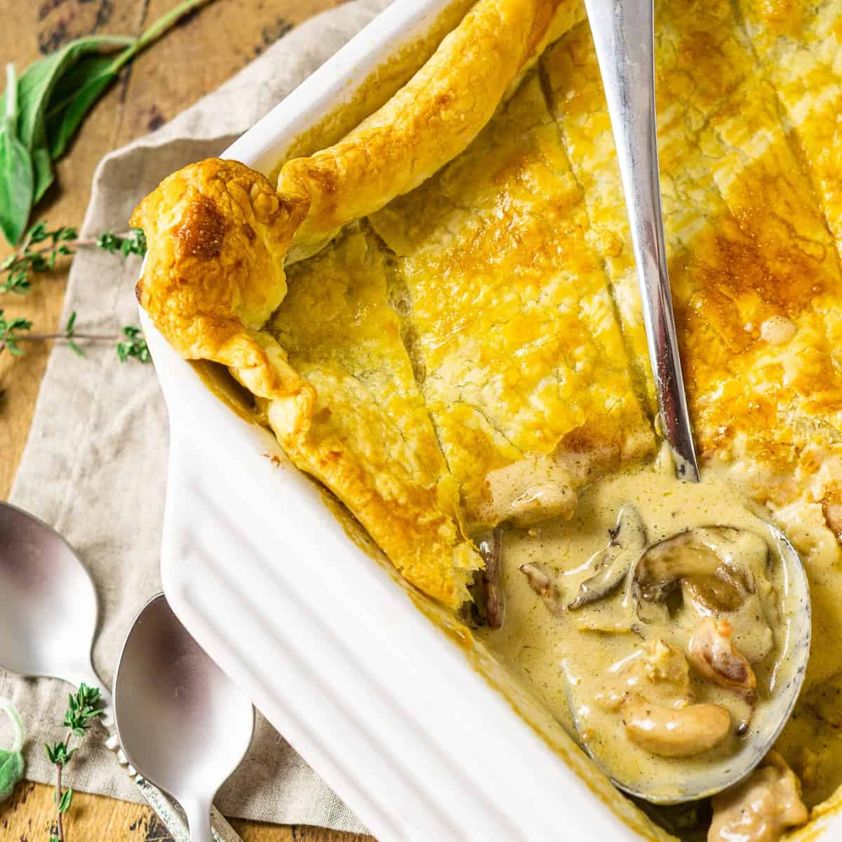 The chicken and mushroom pie with a stainless steel spoon scooping into the dish to show the creamy filling.