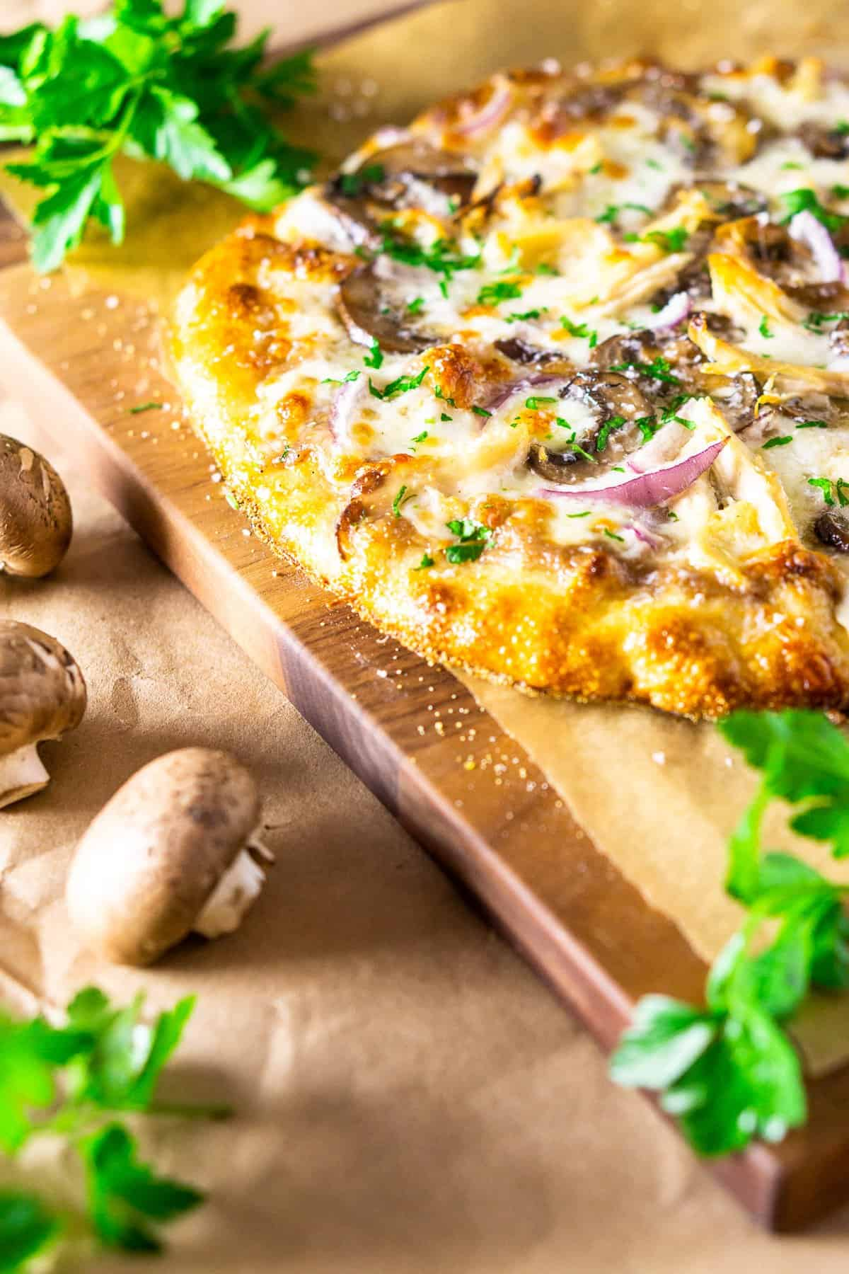 The coq au vin pizza on parchment paper and a cutting board with mushrooms and parsley.