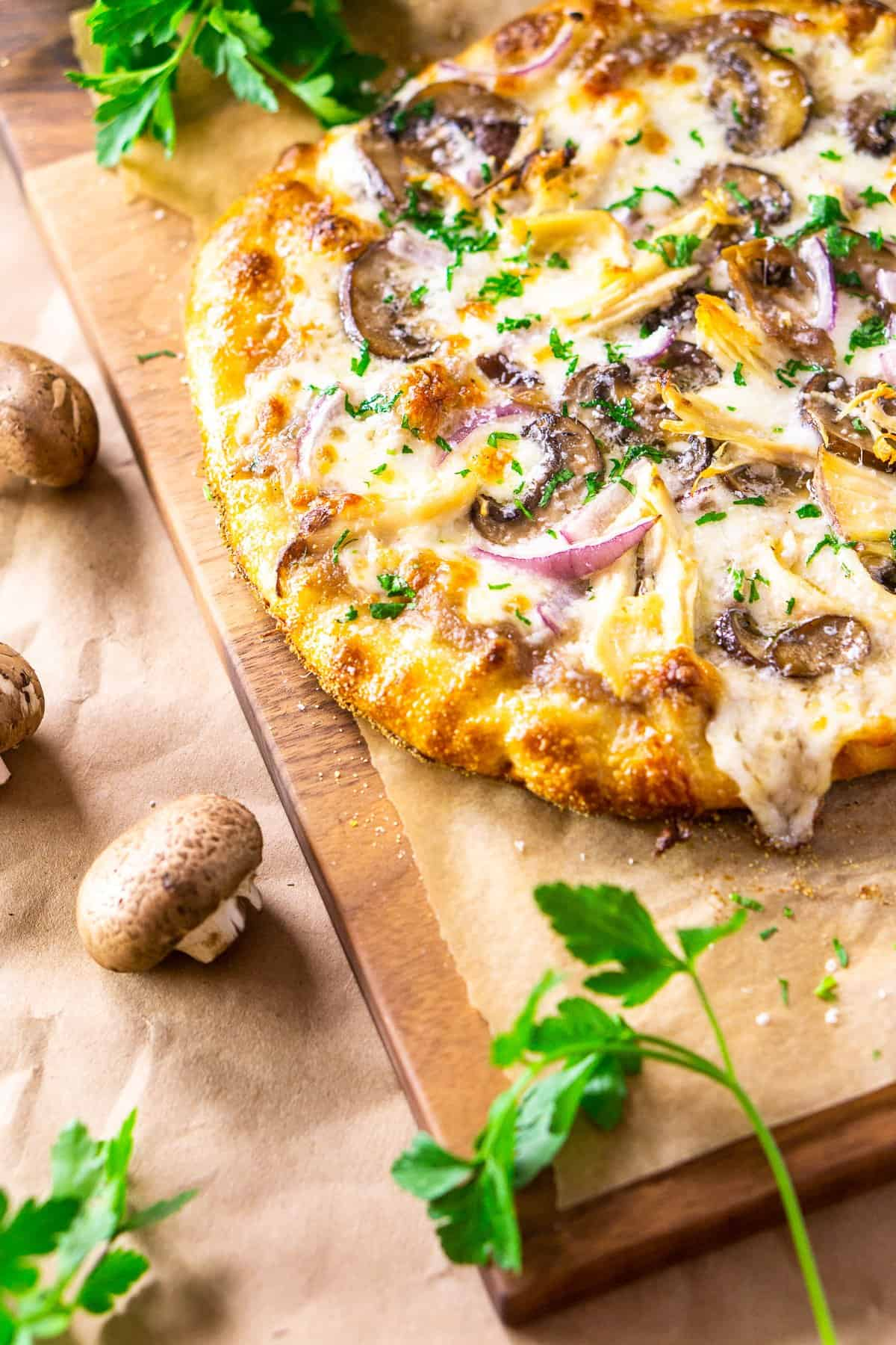 An aerial view of the chicken pizza with fresh parsley and mushrooms around it.