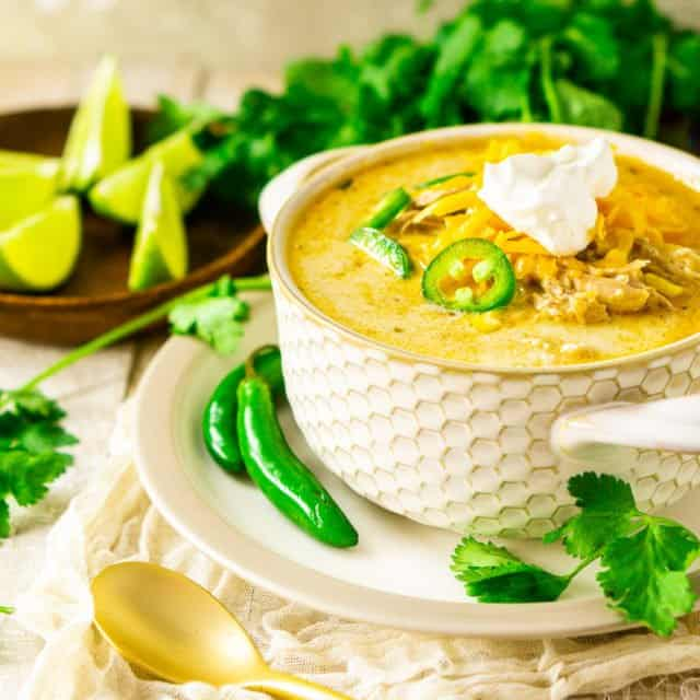 A bowl of the creamy white chicken chili with lime slices and a bunch of cilantro in the background with a gold spoon to the side.