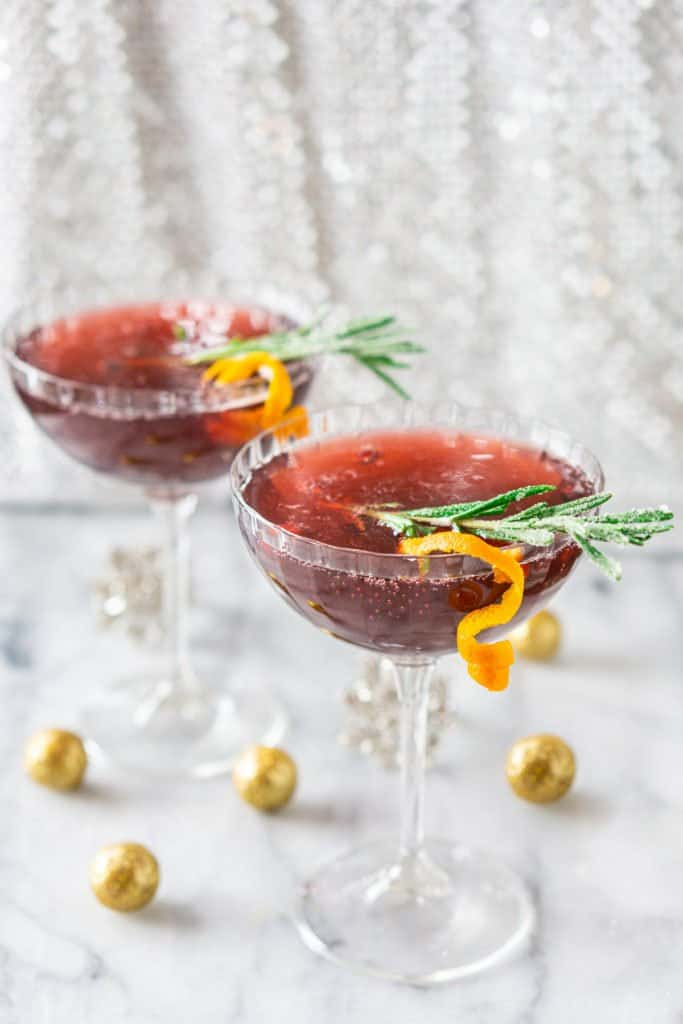 Two sparkling pomegranate cocktails with a silver background and glitter balls surrounding them.