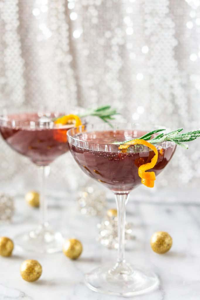 Two pomegranate martinis on a white marble board with festive decor around them.